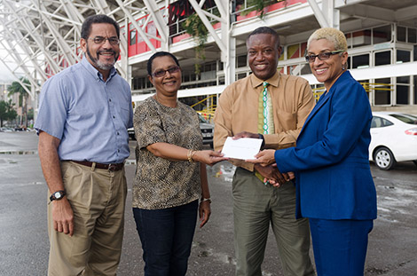 (left) Francis Williams-Smith, Race Director and (right) Diane Henderson, Chairperson of the TT Marathon Committee presents cheque to Ferdinand Bibby, National Director and his associate of Special Olympics Trinidad and Tobago.